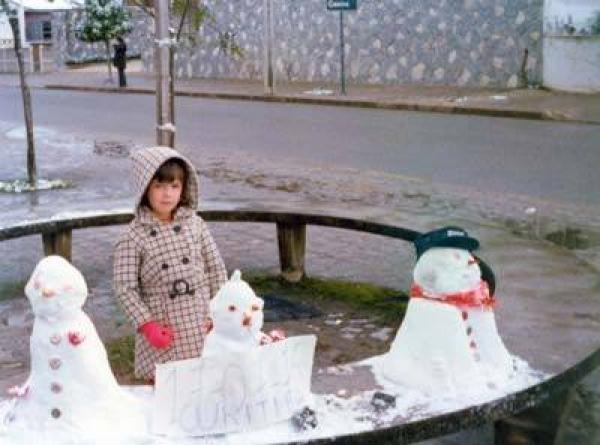 Criança pousa para foto com os bonecos de neve registrando a data da neve de Curitiba em 1975